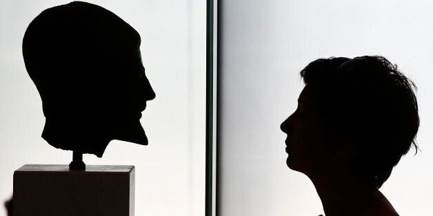 A visitor looks at a head of a bronze statue depicting a bearded hoplite inside the Acropolis museum...