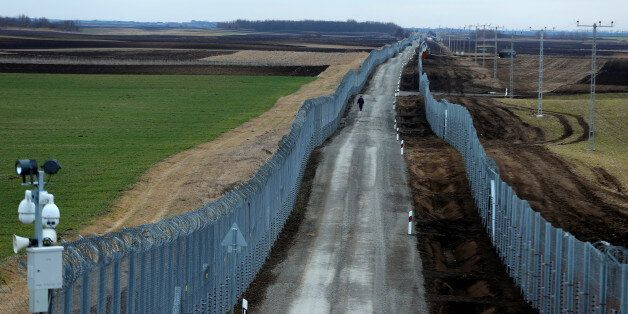 A Hungarian policeman patrols the Hungary-Serbia border, which was recently fortified by a second fence,...