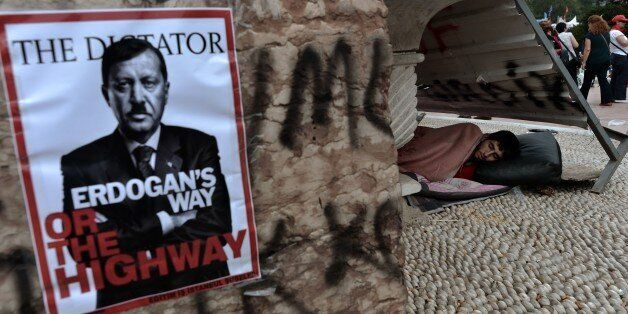 A man sleeps on Taksim square near a poster showing Turkey's Prime Minister Tayip Erdogan portrayed as...