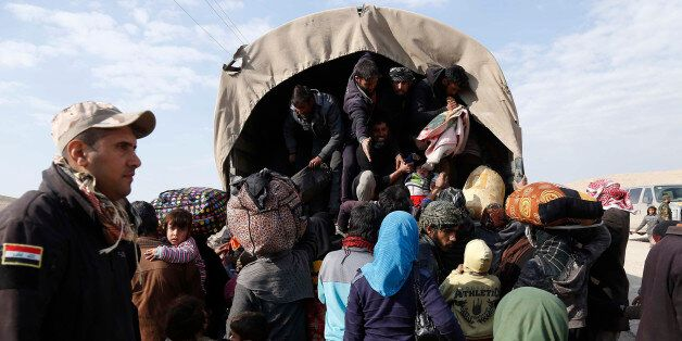An Iraqi soldier watches while displaced civilians board a truck as Iraqi government forces supported...