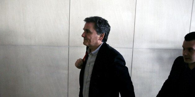 Greek Finance Minister Euclid Tsakalotos arrives at a hotel for a meeting with representatives of the...