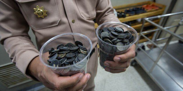 BANGKOK, THAILAND - MARCH 06: An officer shows the coins that the Sea Turtle ate over the years collected...