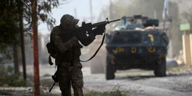 A member of the Iraqi forces aims his weapon as troops advance through Mosul's Jawasaq neighbourhood...