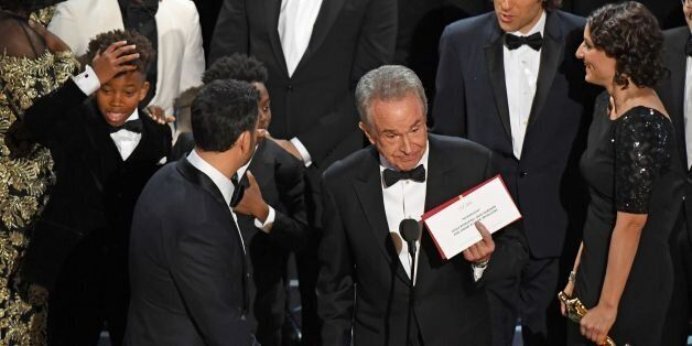 TOPSHOT - The cast of 'Moonlight' and ''La La Land' appear on stage as presenter Warren Beatty (C) shows...