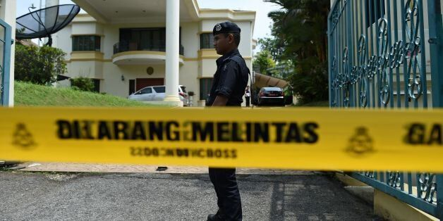 A member of the Royal Malaysian Police keeps watch past a police line drawn across the entrance to the...