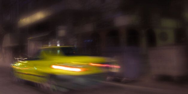 blurred image of a yellow taxi in night