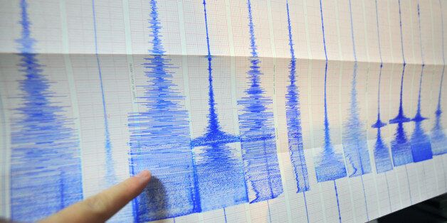A man points at a seismic chart at the Central Weather Bureau in Taipei on March 4, 2010 after a 6.4...