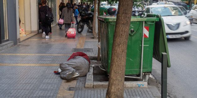 Thessaloniki, Greece - October 24, 2016: Beggar lying by a busy central street. Street beggar lying by...