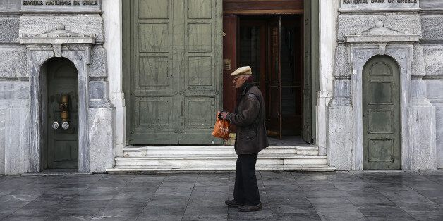 An elderly man walks past the entrance to the headquarters of the National Bank of Greece SA in Athens,...