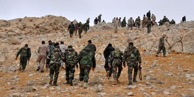 Syrian regime fighters take position as they advance to retake the ancient city of Palmyra, from Islamic...