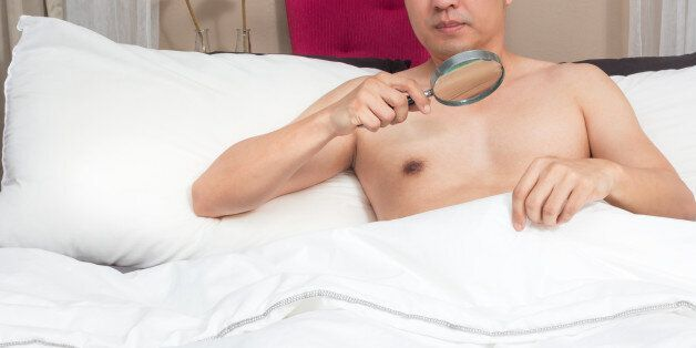 unhappy man with sex problem on bed. concept = too small to see without magnifier