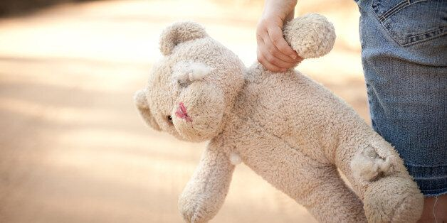 Color stock photo of a little runaway girl holding an old teddy bear at the side of a dirt road in the...