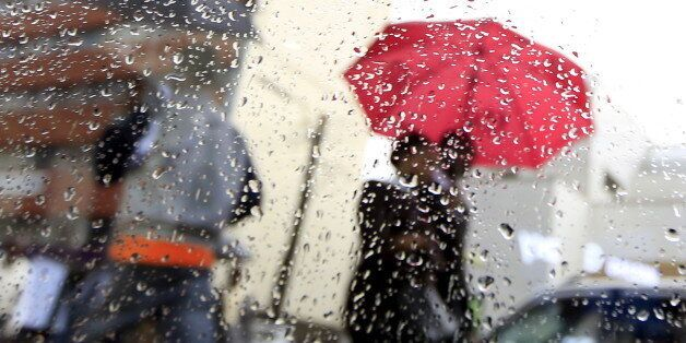 Rain drops are pictured behind a glassy window as people walk home from work during heavy rains in Kenya's capital Nairobi March 9, 2016. REUTERS/Noor Khamis