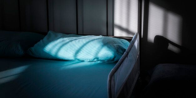 A protective safety side rail guarding the edge of an aging senior adult's bed in a darkened, melancholic...