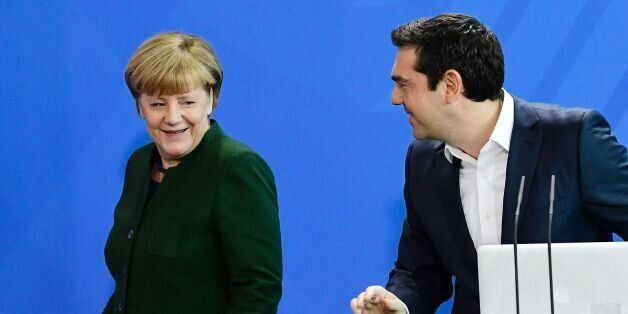 German Chancellor Angela Merkel (L) passes by Greek Prime Minister Alexis Tsipras after delivering a...