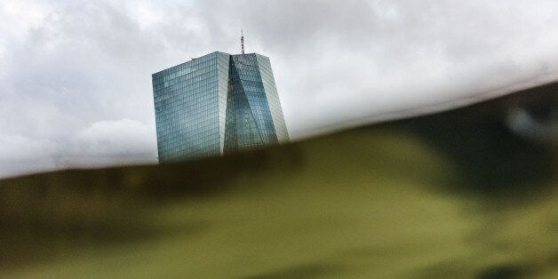 The headquarters of the European Central Bank (ECB) can be seen behind the greenish water of the river...