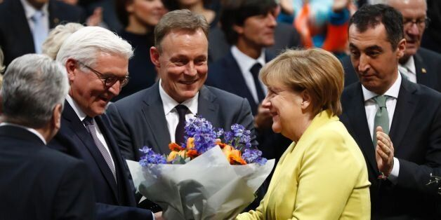 German Chancellor Angela Merkel (R) hands over flowers to new elected German President Frank-Walter Steinmeier...