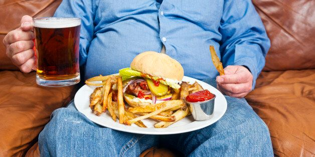 A photo of an overweight man sitting on an old couch with a very large unhealthy meal on his lap and...