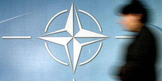 A woman walks past the NATO logo at the entrance of the Alliance headquarters ahead of a NATO foreign...