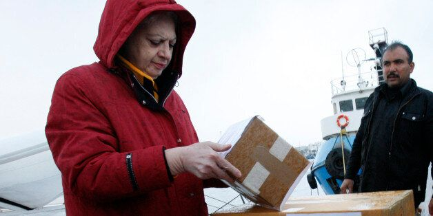 Cypriot Member of Parliament Eleni Theocharous (L) helps load a consignment of medical aid to Gaza on...