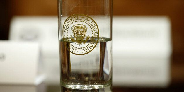 A glass bearing the Presidential seal sits on a table as U.S. President Donald Trump hosts a meeting...