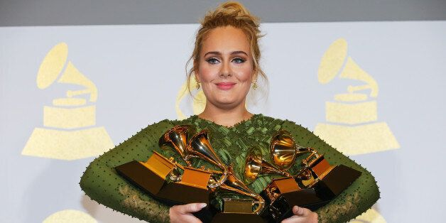 Adele holds the five Grammys she won including Record of the Year