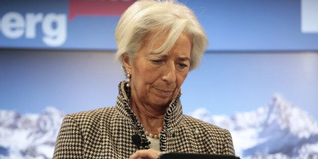 Christine Lagarde, managing director of the International Monetary Fund (IMF), uses a tablet device ahead...