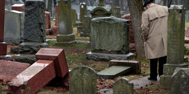 People walk through toppled graves at Chesed Shel Emeth Cemetery in University City on Tuesday, Feb....
