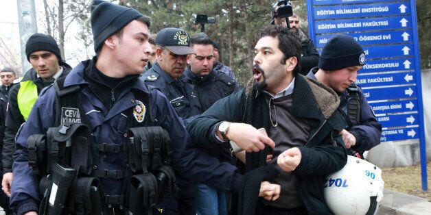 A riot policeman (L) looks at a demonstrator who is detained as Turkish riot police intervene during...