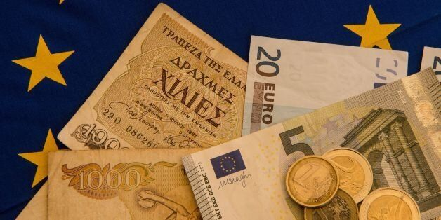 A picture taken on June 29, 2015 in Lille shows Drachma bills, Greece's former currency, next to euro...