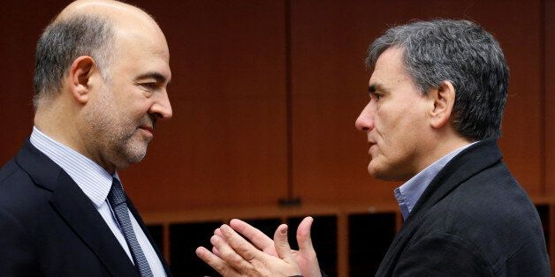 European Economic and Financial Affairs Commissioner Pierre Moscovici listens to Greek Finance Minister...