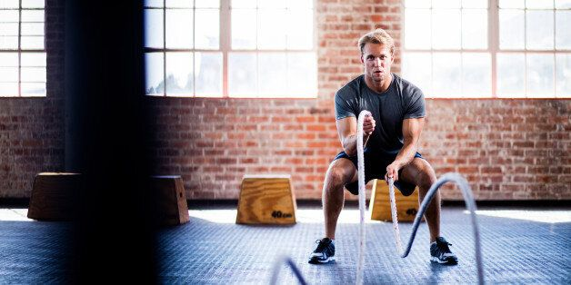 Athletic young adult caucasian man doing battle ropes exercise during a gym training at the gym
