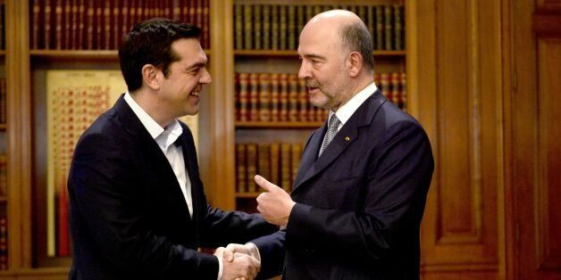 Greek Prime Minister Alexis Tsipras (L) shakes hands with top EU economic affairs official Pierre Moscovici...