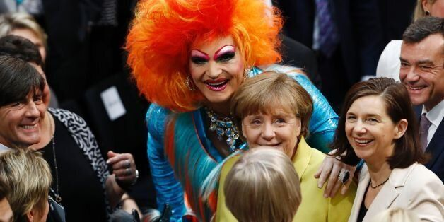 German drag Queen Olivia Jones (C) lays her hand on the shoulder of German Chancellor Angela Merkel (C,...