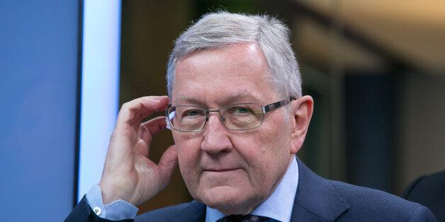 Klaus Regling, chief executive officer of the European Financial Stability Facility (EFSF), adjusts his...