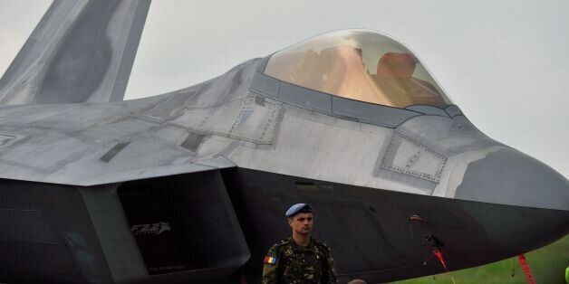 A Romanian army serviceman stands next to an US fight jet F-22 Raptor at the Mihail Kogalniceanu Air...