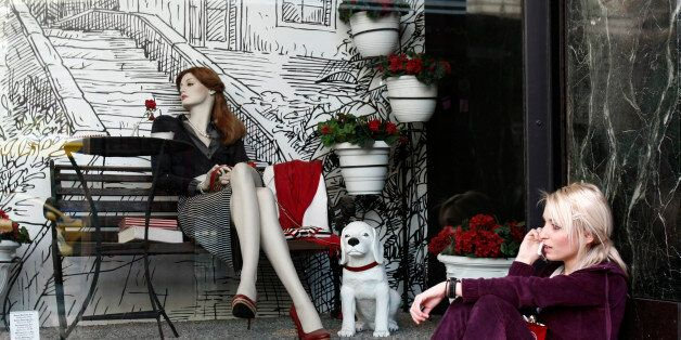 A woman sits in front of a shop window outside a department store in central Athens April 30, 2010. Greek...