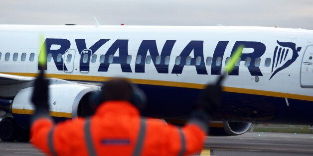 An employee uses glow sticks to guide a Ryanair Holdings Plc aircraft into position at Dublin Airport,...