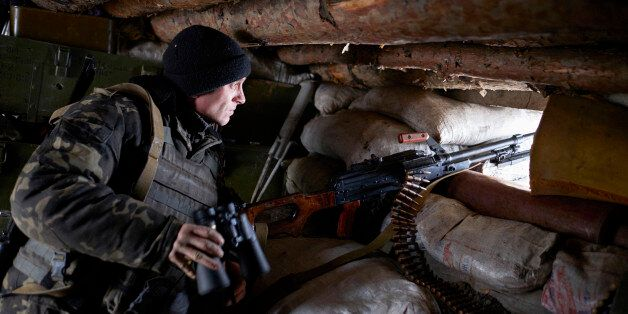 AVDIIVKA, UKRAINE - JANUARY 8: A Ukrainian serviceman stands guard in a trench in the frontline city...
