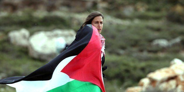 A woman holds up the Palestinian flag during clashes with Israeli soldiers close to the Jewish settlement...