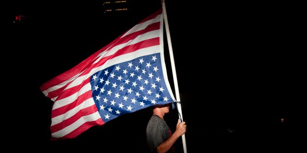 TAMPA, FL - AUGUST 30: A protester with an upside-down American flag marches on the last night of the...