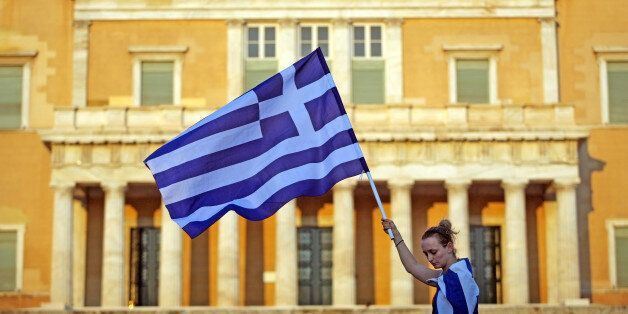 Athens, Greece - June 30, 2011: A Greek woman holds a flag in front of the Greek parliament during a...