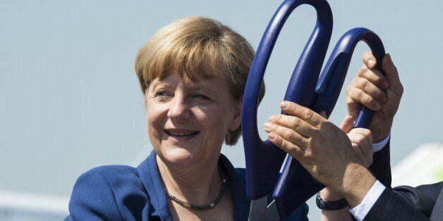 German Chancellor Angela Merkel holds scissors during the opening ceremony of the International Air Show...