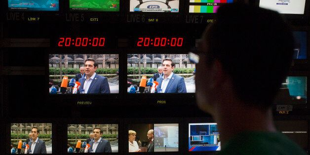 Alexis Tsipras, Greece's prime minister, center, is seen on television monitors in the television production...
