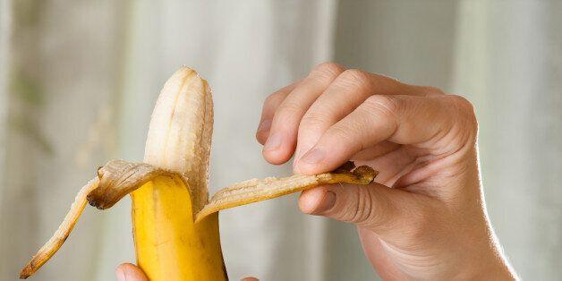hands peeling ripe yellow banana, close
