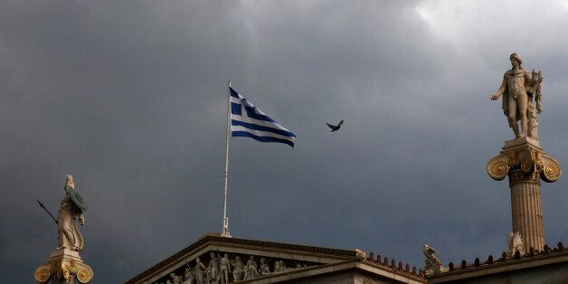 A Greek national flag flutters atop the university building as dark clouds fill the sky in Athens, Greece,...