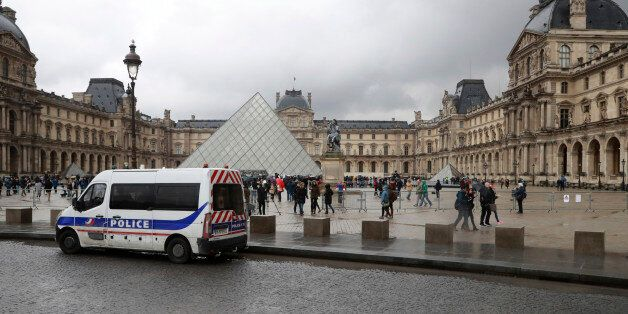 People walk past a police vehicle parked in front of the Louvre Pyramid in Paris on February 4, 2017...