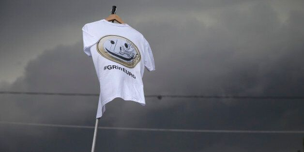 Dark clouds fill the sky as a Pro-Euro protestor holds a T-shirt with a
