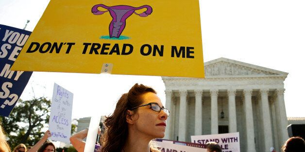 Demonstrators hold signs outside the U.S. Supreme Court as the court is due to issue its first major...