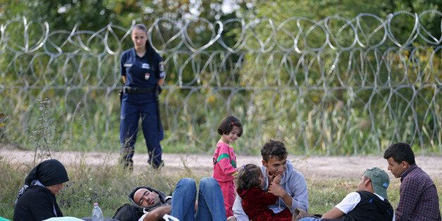 Migrants sit on the field as they were stopped by the Hungarian police after illegally crossing from...